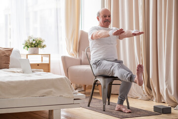 Elderly man practicing yoga asana or sport exercise for legs and hands on chair