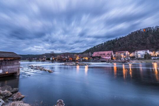Staustufe und Wasserwehr des Fluss Regen in Markt Regenstauf in der Oberpfalz im Zwielicht zur blauen Stunde Abends während der Dämmerung, Deutschland