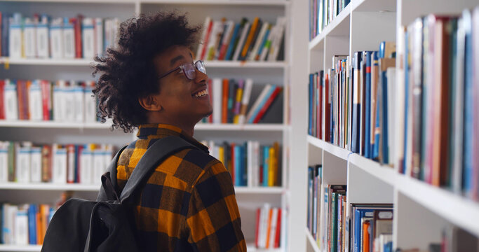 Back view of young happy african student looking around in modern library
