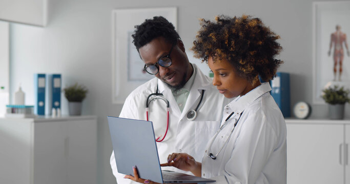 African team of doctors working on laptop in medical office
