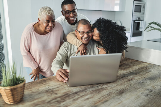 Happy black family doing video call at home - Main focus on son face