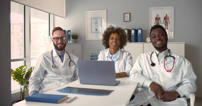 Diverse medical colleagues sitting at desk chatting and laughing in clinic office