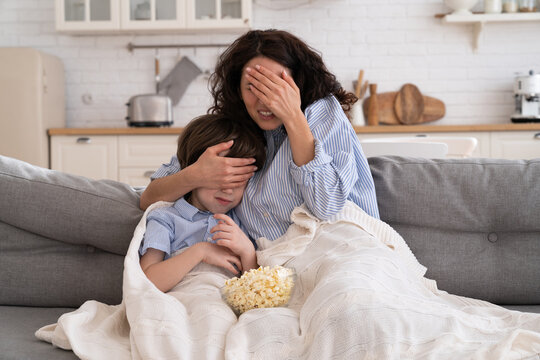 Frightened mom and little kid son with bowl of popcorn watching scary scene in movie closing their eyes, sitting on sofa at home. Mother hugs the child, watches a horror movie, feels fear.