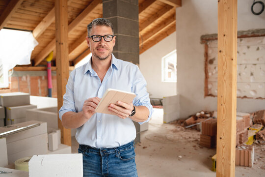 male architect middle age with black glasses stands on construction site in loft house and holds his tablet