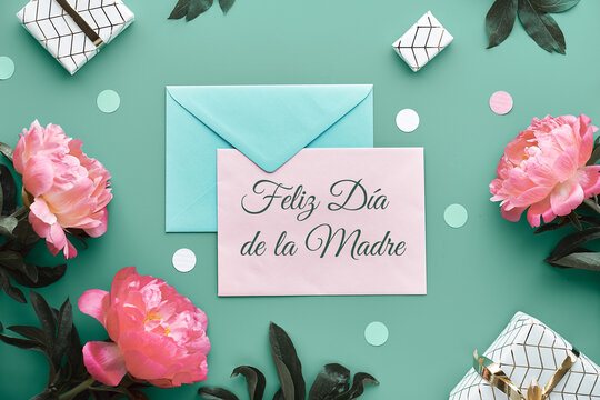 Feliz Dia de la Madre means Happy Mother's Day in Spanish. Pink peony flowers, wrapped gifts tied with gold ribbon, confetti. Mint green, pink floral decor. Pastel colors, lat lay, top view on paper.