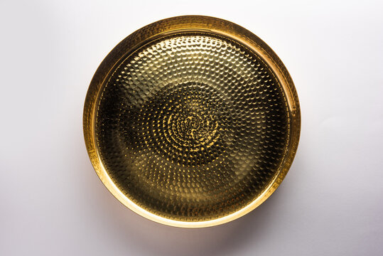 Empty brass or gold oval or round shape plate or thali over white background