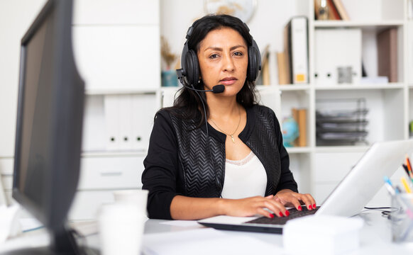 Portrait of experienced female customer support phone operator with headphones during work in call center
