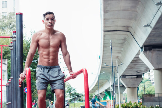 Young, athletic Latino male doing muscular exercise in the open air.