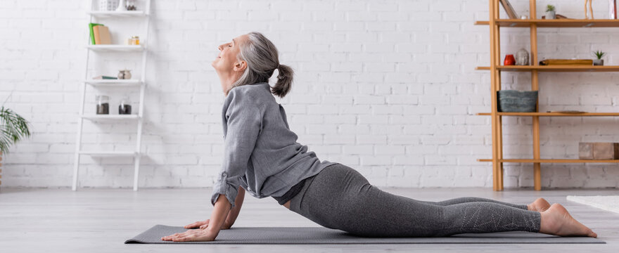 side view pleased middle aged woman in cobra pose practicing yoga on mat at home, banner