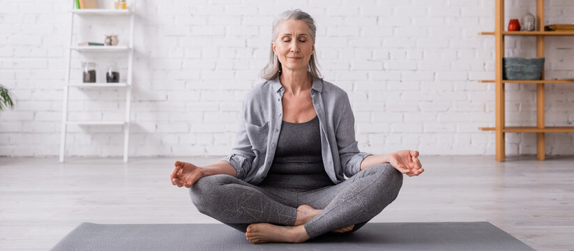 mature woman with grey hair sitting in lotus pose on yoga mat, banner