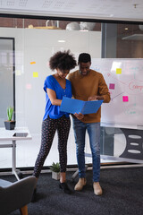 Diverse male and female colleagues standing having discussion with whiteboard in background