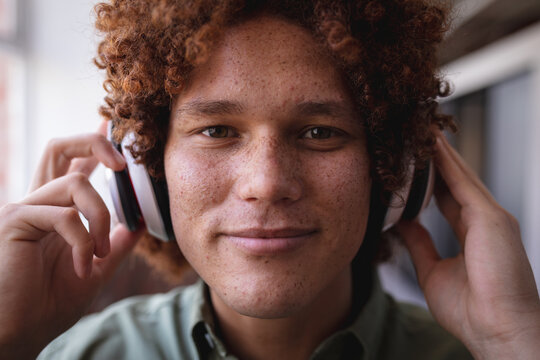 Portrait of happy mixed race businessman standing in office and wearing headphones