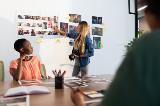 Diverse group of business colleagues brainstorming looking at photos in meeting room