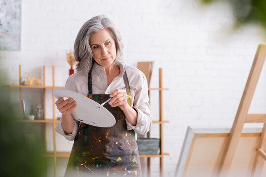 pensive mature woman in apron holding paintbrush and palette while looking at canvas