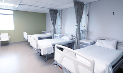 General view of an empty hospital room with three beds