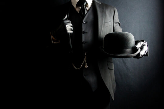 Portrait of Businessman in Dark Suit and Leather Gloves Holding Bowler Hat. Concept of Classic British Gentleman. Retro Fashion and Vintage Style.