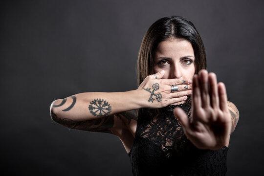 bellissima ragazza  mora con i tatuaggi scopre la bocca e fa il segno dello stop con l'altra mano, isolata su sfondo nero