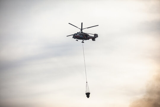 Fire fighting helicopter silhouette with bambi bucket for сarrying water to put out a massive building city fire, process of put out a large blaze bush fire wildifre, aerial firefighting with chopper