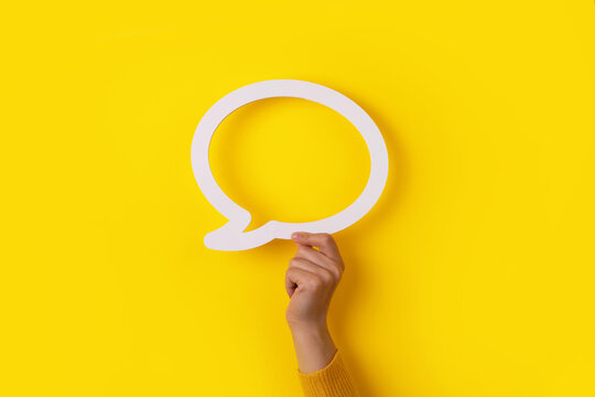 hand holding dialogue bubble over yellow background