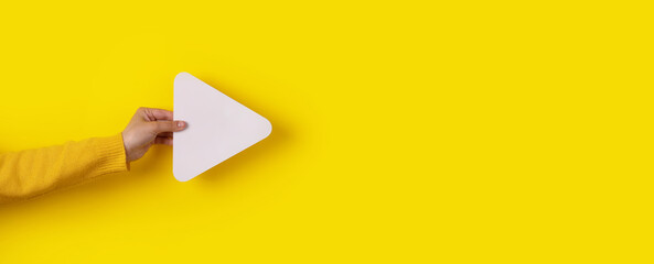 Fototapeta hand holding media player button icon over trendy yellow background, panoramic layout