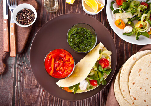 mexican vegan tortilla wrap with vegetables and sauce dips on the dinner table