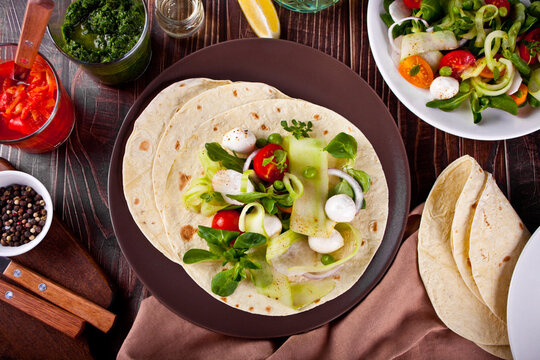 mexican vegan tortilla wrap with vegetables on the dinner table