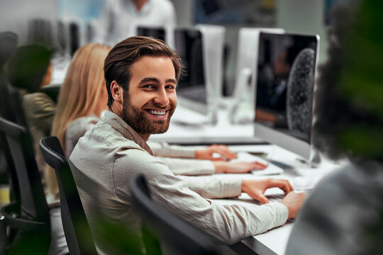 Handsome business man works at the computer with colleagues in the office and smiles looking at the camera. Data analysis, statistics, finance. Training, business team, programming, development.