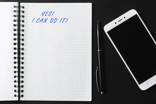 Motivational quote yes I can do it! An open notebook, a black pen, and a white smartphone on a dark background.