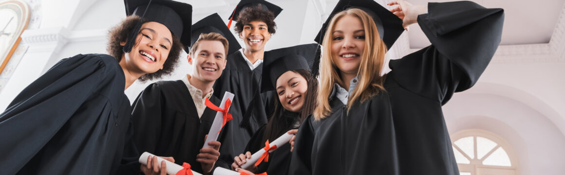 Low angle view of smiling interracial graduates holding diplomas, banner
