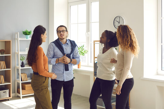 Intelligent young diverse business people or coworkers communicating, discussing work and exchanging opinions in informal office meeting. Group of interested women listening to smart male colleague