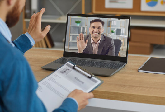Smiling male employer or business personnel recruiter greeting job candidate who applied for vacancy. View over shoulder of working desk and laptop computer screen during virtual online job interview