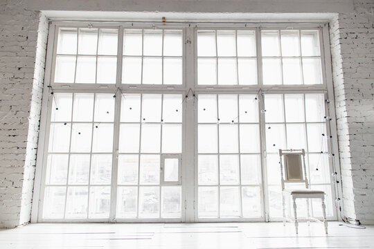 Bright photo studio with big window, high ceiling, white wooden floor