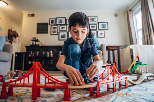 Boy playing with toy train in living room