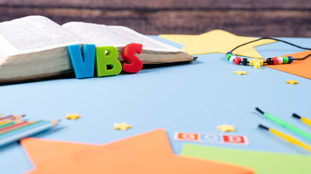 """Church background with Abbreviation """"VBS"""" (Vacation Bible School) next to black bible . Copy space text. Selective focus."""