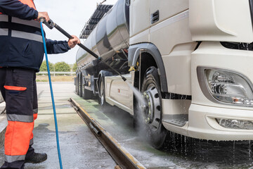 Tank truck driver cleaning the exterior of the vehicle.