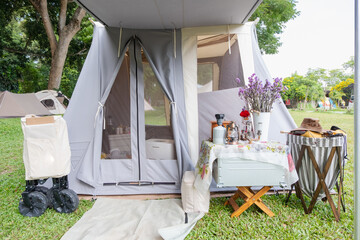 Fototapeta Decoration gray teepee tent with luxurious glamping interior with A lamp and a beautiful flower vase are placed on the table at camping area ,holiday,Camping
