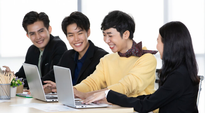 A group of multi-sex colleagues businesspeople, tomboy and transgender gay, working together with happy and intimate manner with laptop notebook computer in office