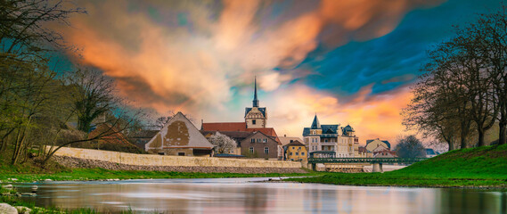 Fototapeta medieval castle by the river in a small European town