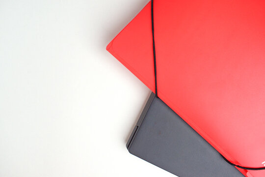 On a white table, the edge of a gray laptop and a red folder. Online learning concept.
