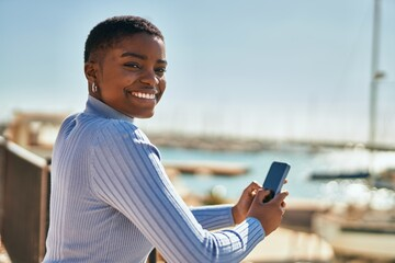 Fototapeta Young african american woman smiling happy using smartphone at the port obraz