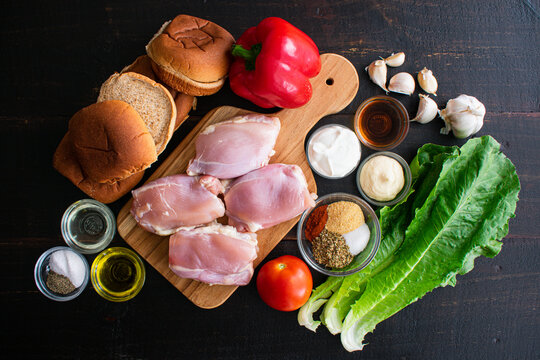 Portuguese Chicken Burger Ingredients: Raw chicken thighs, hamburger buns, vegetables, and spices on a wooden background