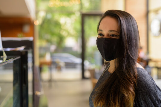 Portrait of woman wearing face mask for protection against coronavirus Covid-19 at restaurant