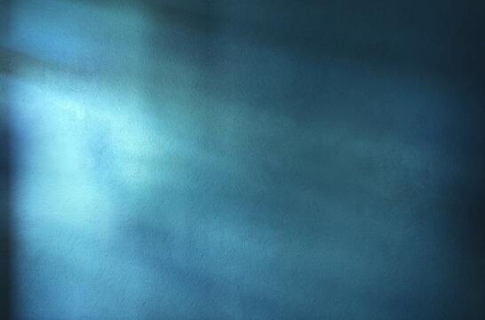 Abstract blue wall texture. Illuminated by beams of light. Empty room scene.