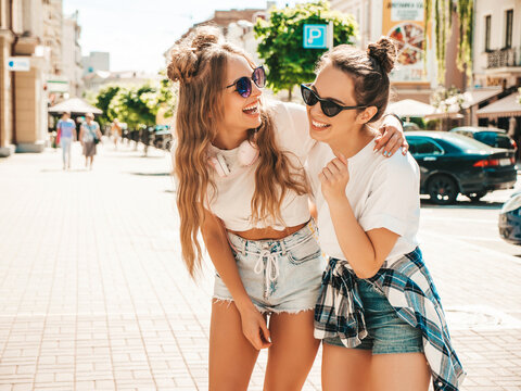 Portrait of two young beautiful smiling hipster female in trendy summer white t-shirt clothes.Sexy carefree women posing on street background. Positive models having fun, hugging and going crazy