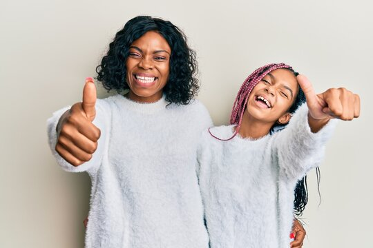 Beautiful african american mother and daughter wearing casual winter sweater approving doing positive gesture with hand, thumbs up smiling and happy for success. winner gesture.