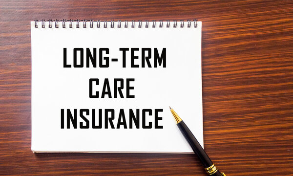 LONG TERM CARE INSURANCE information close-up written on a notepad and a wooden background. Medical concept
