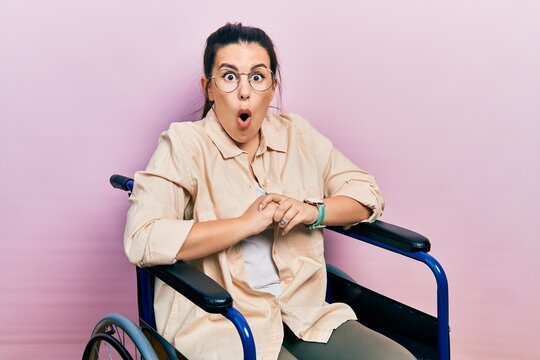 Young hispanic woman sitting on wheelchair afraid and shocked with surprise and amazed expression, fear and excited face.