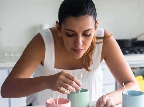 latina woman making candles in home