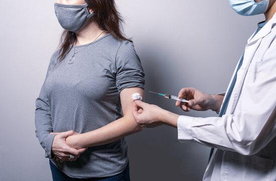 Doctor latino dando vacuna Covid-19 o antivirus contra la gripe inyectada a un paciente mujer que usa mascarilla protectora contra la enfermedad del virus en la clínica de salud o en el hospital.