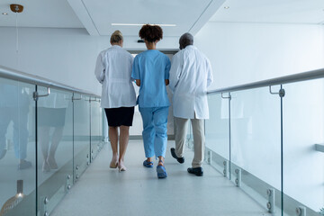 Three diverse male and female doctors walking through hospital corridor talking